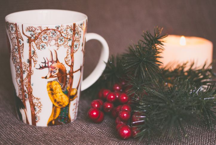 white and gold mug with stag playing flute, in background is a candle, ferns and red berries